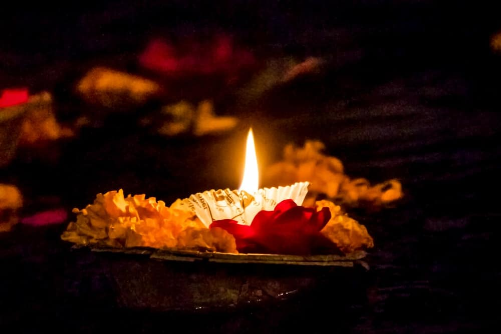 a candle upon a Lilly pad floats in the dark